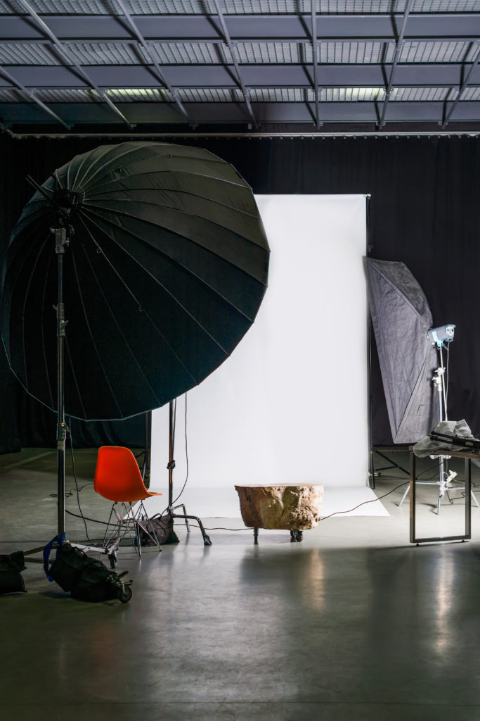 Empty photo studio with modern interior and lighting equipment. Preparation for studio shooting: empty chair and studio lighting